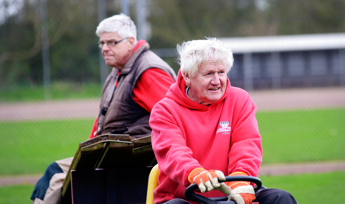 2 senioren die op een tractor vrijwilligerswerk doen